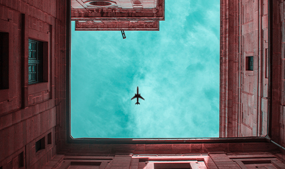 Surrounded by buildings while looking upward to an airplane in the sky