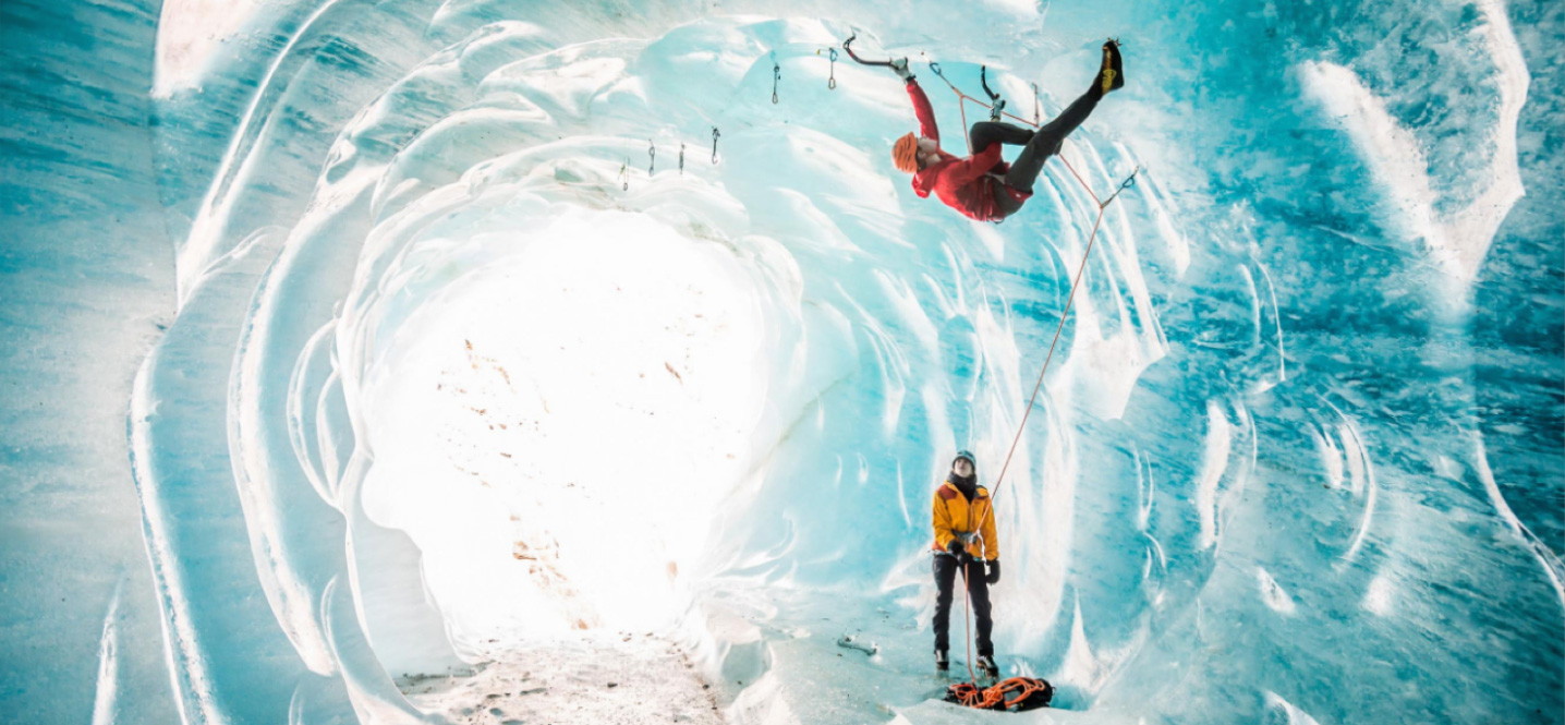 Person ice climbing while another belays